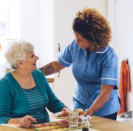 caregiver preparign a lunch to a senior woman