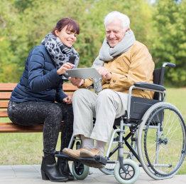 caregiver and senior man looking at a tablet