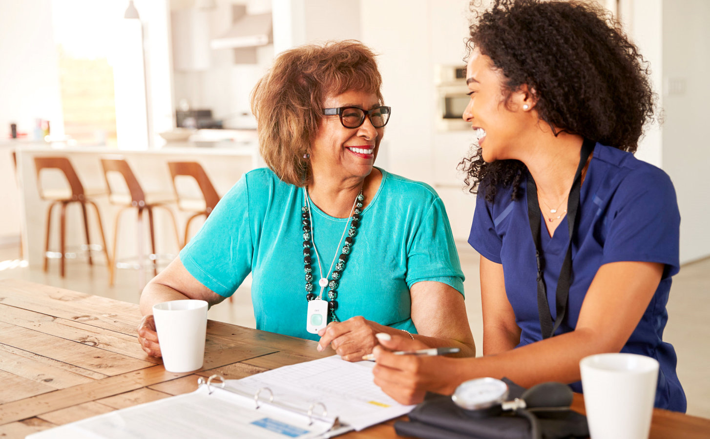 caregiver and a senior woman happily writing on a pad