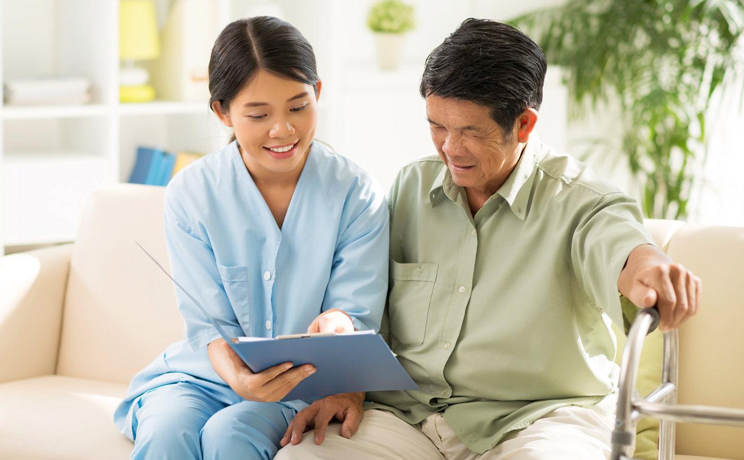 caregiver and a senior man looking at a pad