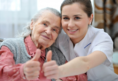 a caregiver and a senior woman showing thumbs up