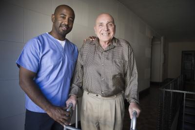caregiver and a senior man smiling