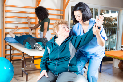senior patient doing an exercise  while assisted by a caregiver