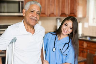 caregiver with stethoscope assisting a senior man