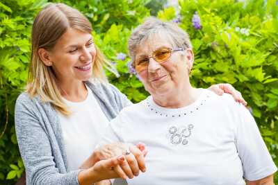caregiver holding the hand of a senior