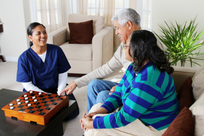 two senior couple playing game with their caregiver