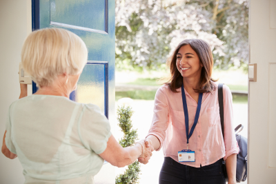 senior woman greeting female caregiver making home visit