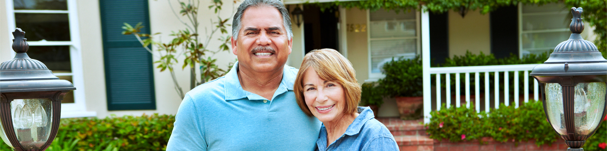 senior couple smiling in front of a house